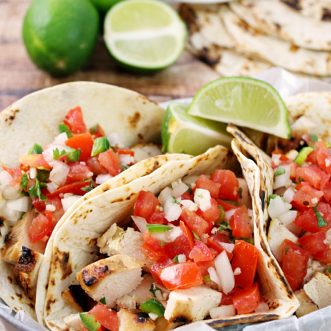 Grilled Chicken Fresco Tacos in a metal bowl lime slices.