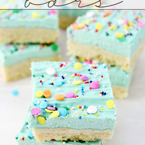 Sugar Cookie Bars stacked on parchment paper.
