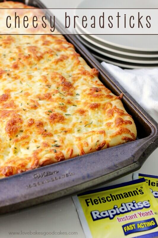 Cheesy Bread sticks in a baking sheet with a stack of plates.