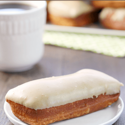 Maple Bar on a white plate with a cup of coffee.
