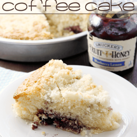 Blueberry Lemon Crumb Coffee Cake on a white plate with a jar of jam.
