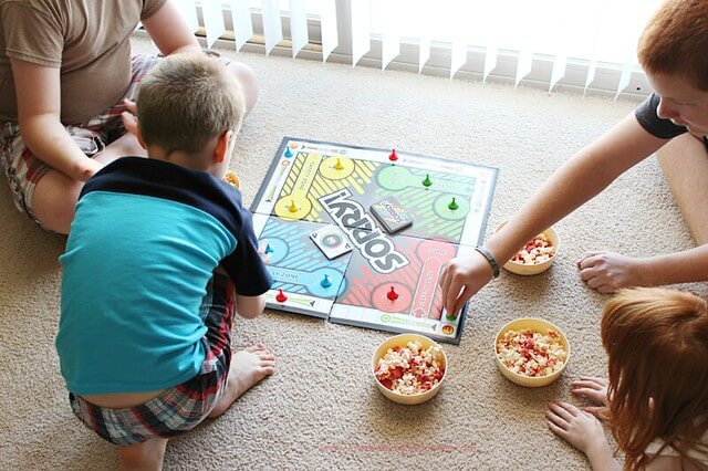Four kids playing a board game while eating popcorn.
