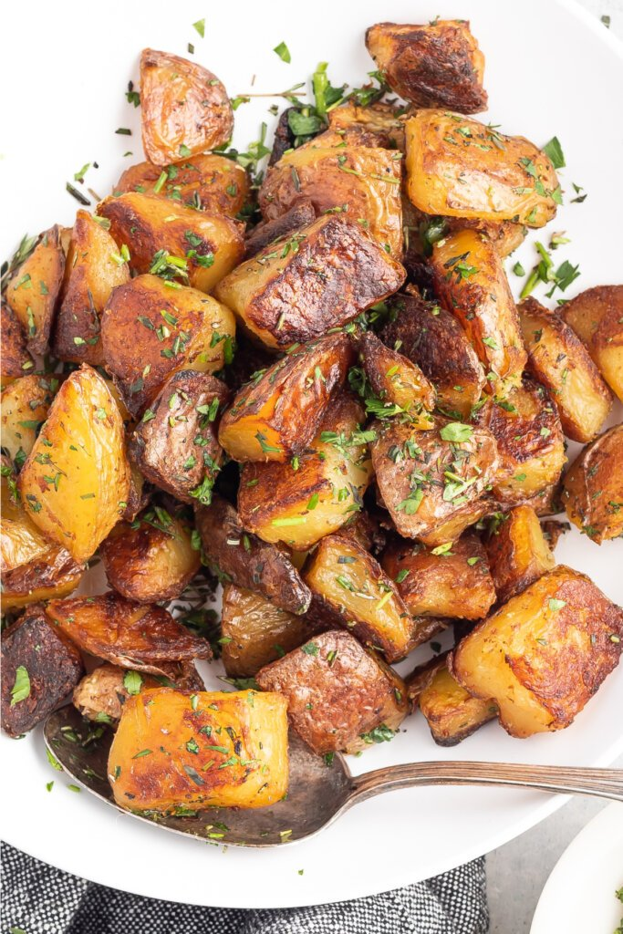 crispy herb roasted potatoes in serving bowl with spoon