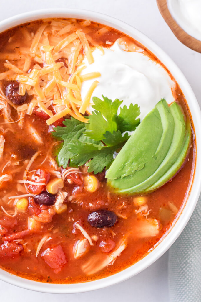 looking down into a bowl of chicken enchilada soup garnished with cheese, sour cream, and avocado slices
