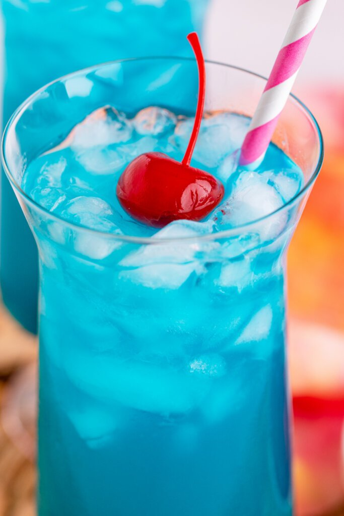 looking into a long tall glass with ocean water cocktail with a maraschino cherry and straw on top