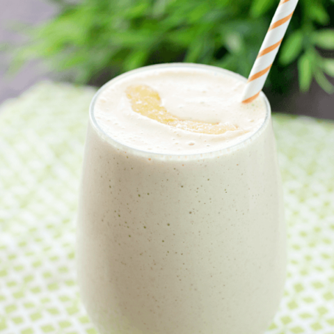 Peach & Oatmeal Smoothie in a glass with a straw.