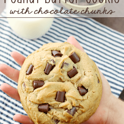 Giant Peanut Butter Cookie with Chocolate Chunks in someone's hand with a glass of milk.