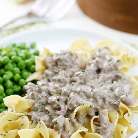 Hamburger Stroganoff on a white plate with peas.