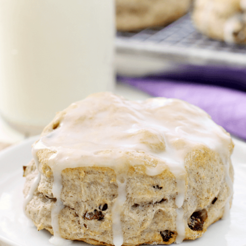 Cinnamon Raisin Biscuit on a white plate with a glass of milk.
