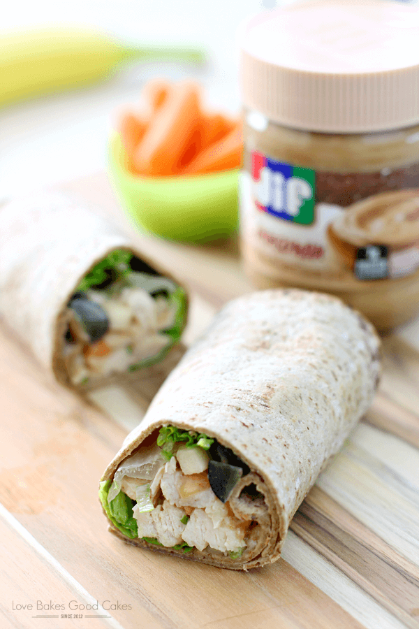 PB Apple Chicken Salad Wraps with the ends opened up to see the ingredients. Close up with a jar of Jif in the background.