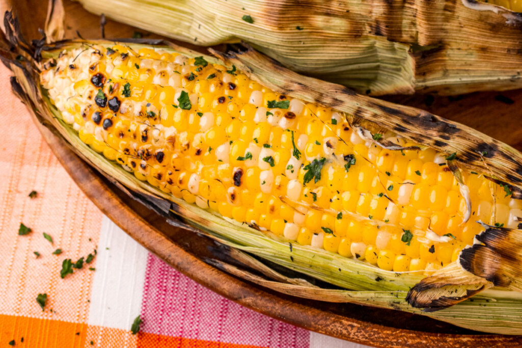 grilled corn in husk in wooden serving bowl