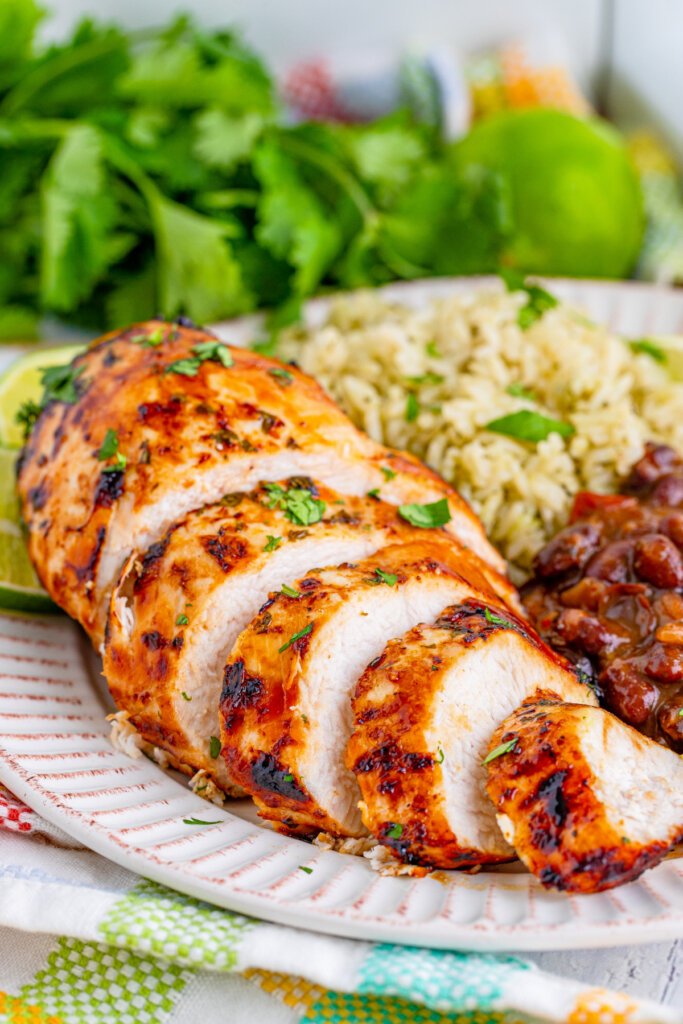 sliced air fryer margarita chicken on plate with rice and beans