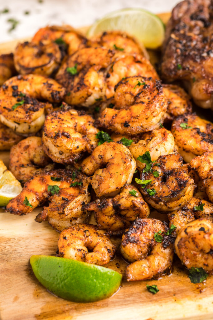 blackened shrimp piled on a wooden board