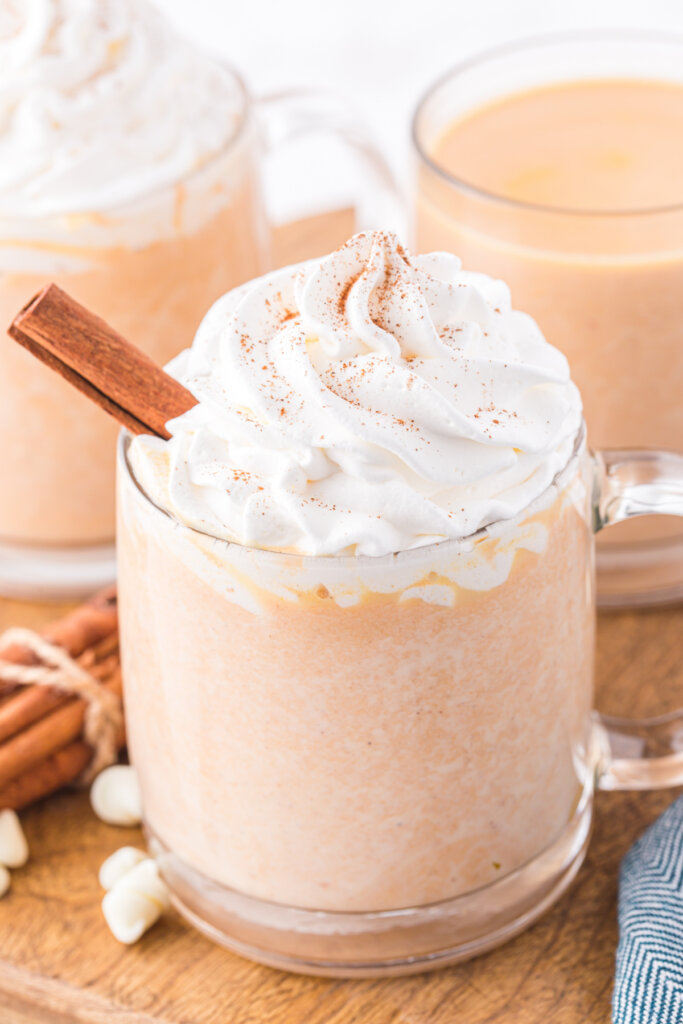 clear glass of pumpkin spice white hot chocolate topped with whipped cream