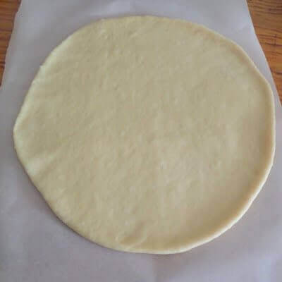 Rolling out the dough flat.